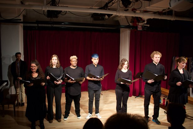 Seven actors dressed in all black stand in front of a red curtain and read from binders of scripts in their hands.