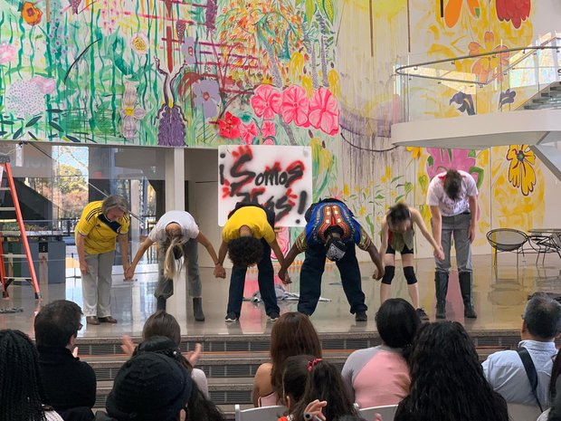 "Six people bowing at the front of a stage, the backdrop of which is covreed in brights, splattered paint and graffitti, and a sign that reads ""Somos Mas!"""