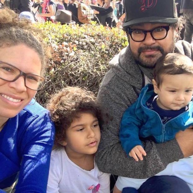 Mando Alvardo and his family sit in the park and smile into the camera. All wear different shades of blue.