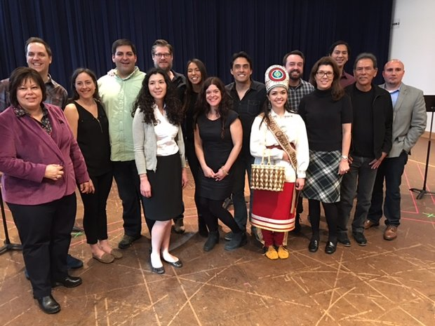 Eastern Band of Cherokee Indians Tribal Council members, Secretary of State Terri Henry, and Cherokee royalty at workshop reading. 14 people, one in traditional Cherokee clothing stands in the front. Behind them, music stands and a black curtain.