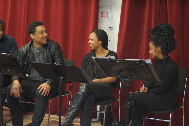 three actors sit at music stands in front of a red curtain. they are smiling