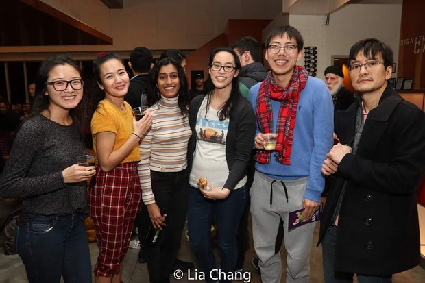 Lauren Yee and other artists gathered in Signature Theatre's lobby, holding drinks and smiling.