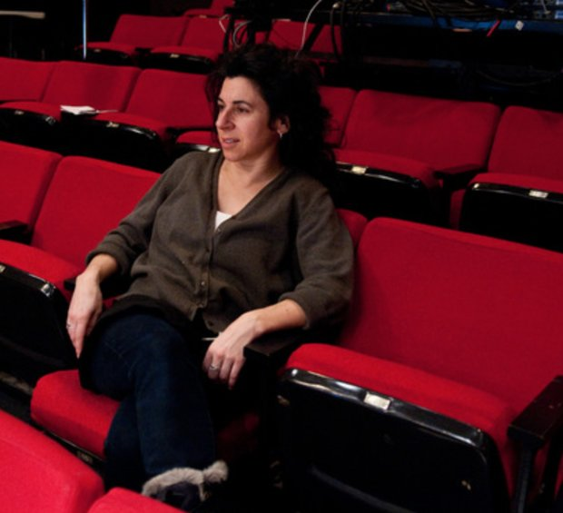 Katie Pearl sits alone in a theater on a red plush chair.