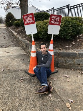 "Gregg Mozgala sits between two traffic cones, each holding up a sign that reads ""Special Needs Parking"""