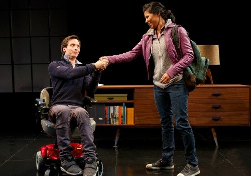 Gregg Mozgala, in a wheelchair and acting as John in Martyna Majok's COST OF LIVING, shakes the hand of actor Jolly Abraham.