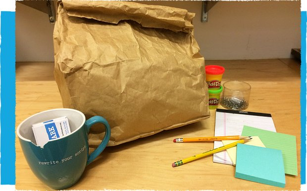 "A brown paper lunch bag sits on a desk with a blue mug, filled with lark business cards, that says ""rewrite your script."" Assorted pencils and notepads lay nearby, along with two containers of play-doh."