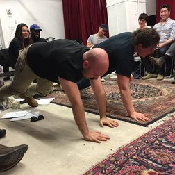 Rob Askins and Lucy Thurber doing push ups in The Lark's BareBones Studio.