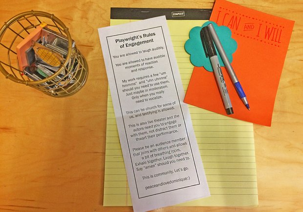 "A yellow legal pad lies on a wood surface. On top of it are a pad of blue sticky notes in the shape of a flower, two pens, a smaller, orange pad of paper, and a white slip of paper that reads ""Playwright's Rules of Engagement."""