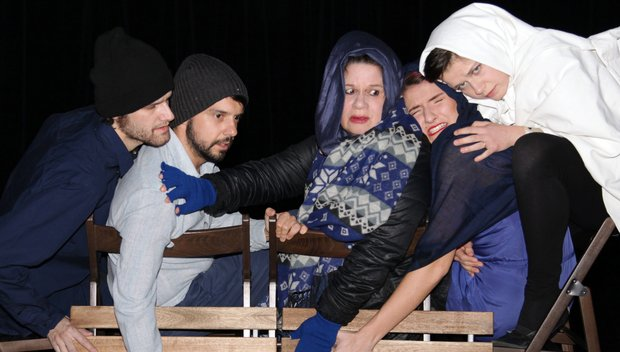 Five actors, dressed all in blue, black, or white, each wearing some kind of head covering (hats, hoods, and hijabs) crowd onto two wooden chairs onstage, looking scared.