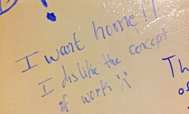 "blue marker on dry erase board reads ""I want home!! I dislike the concept of work"""