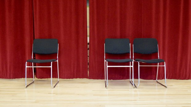 Three empty chairs in front of a red curtain.