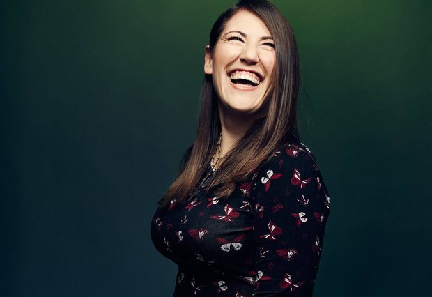 Against a dark, forest green background, Madeline Sayet tilts her head upwards, looking slightly over her shoulder and laughing.