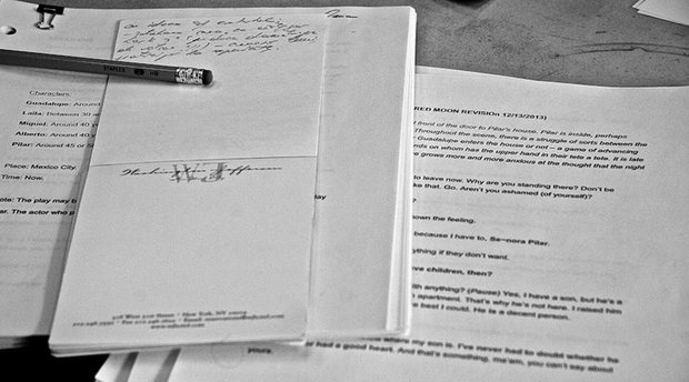 Black and white: Pages from a script are laid out on a table, some are binder clipped together. A pencil and a notepad with handwritten notes rest on top of the pages.