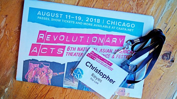 "A folded flier sits on a wood surface. In bright pink block letters it reads ""Revolutionary Acts. 6th National Asian American Theater Conference and Festival."" A nametag reading ""Christopher Reyes, The Lark"" sits on top, partly obscuring photo of dancers"