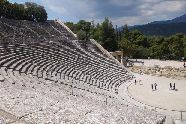 An open air theater, stadium style, made of stone. It is huge. A few people stand in the stage area. The seats are completely empty except for a couple of people walking up the stairs.