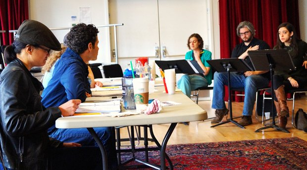 A studio rehearsal room with large windows and red curtains. Kimber Lee sits at a fold out table with Thomas Kail as they watch actors at music stands read from scripts.