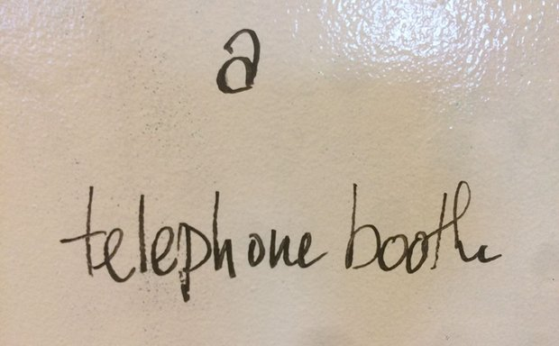 "dry erase board reads ""a telephone booth"""