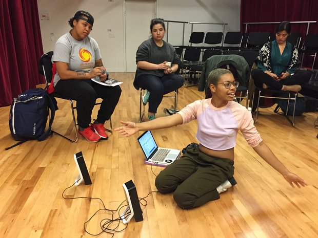 Aya Lane kneels on the ground on The Lark's BareBones studio, in front of a laptop and speakers. Her arms are spread wide as she addresses the artists sitting in chairs around her.