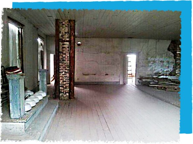 An old masonic meeting hall. A dark and empty room with white floors and a brick support beam in the center.