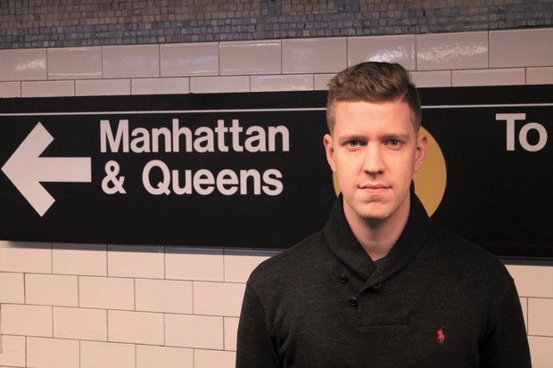 "Francisco Mendoza stands in a subway station, in front of a sign that reads ""Manhattan & Queens."" A yellow circle is visible behind him, though the letter on it that indicates the train line is obscured"
