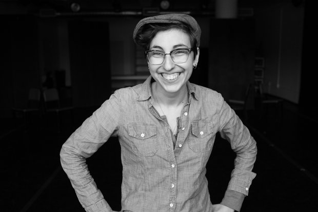 A black and white photo of Christina Quintana standing with her hands on her hips and smiling straight into the camera. She wears glasses, a button down shirt, and a newsboy style cap.