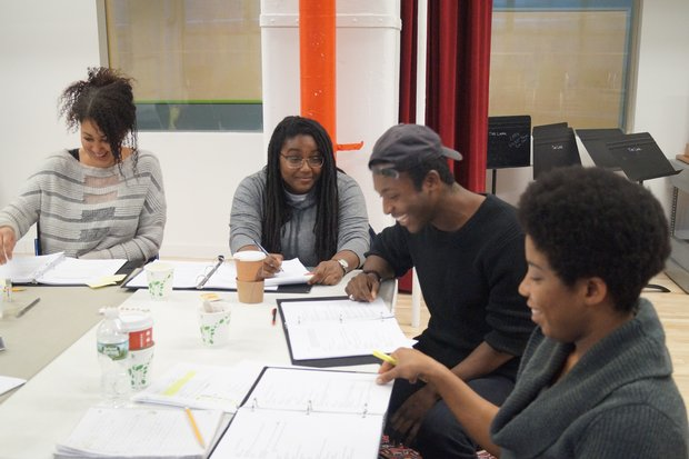 Playwright, Actors, and Director work around a table rehearsing a new play.