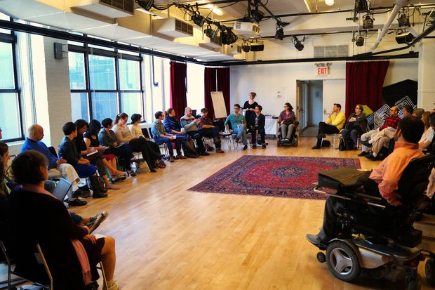 A large circle of theater artists, both disabled and non disabled, sit in a circle in The Lark's BareBones Studio, a large, bright room with wood floors and an ornate red rug in the center. Large windows sit at the left of the frame and light the room.