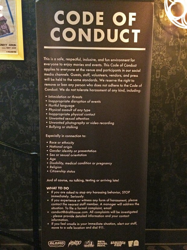 A sign displayed in the lobby of the Alamo Drafthouse movie theater labelled Code of Conduct that details the theater's policy for not tolerating harassment. For the full text of the sign, follow link in the text below.