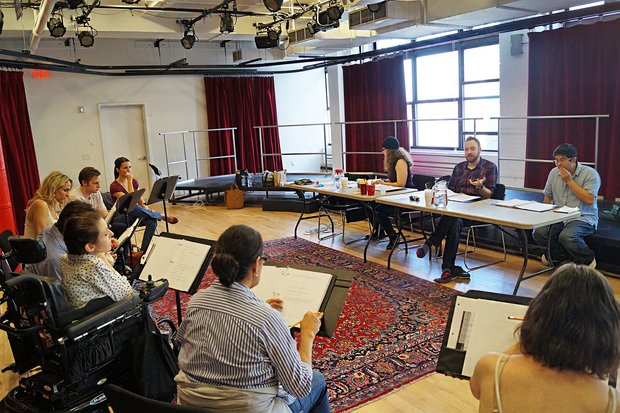In a large studio seven actors sit in front of music stands, across from the director (Moritz Von Steupnagel), playwright (Mike Lew), and stage manager, seated at folding tables on the opposite side of a patterned red rug.