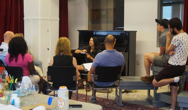 A rehearsal for a reading. The director sits in the center, facing the camera. We see the backs of the rest of the creative team as they focus on her. Playwright MJ Kauffman sits to the right ontop of a piece of rehearsal furniture.