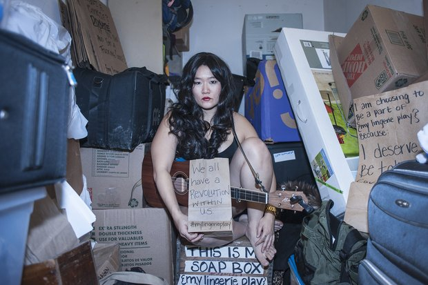 "Diana Oh sits in the center of a cluttered room holding a paper bag that reads ""We all have a revolution within us. #mylingerieplay"""