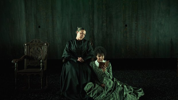 Actors on stage. One woman sits in a grand wooden chair, the other kneels beside her reading a book. The stage is dark and lit faintly with green.