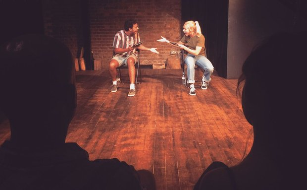 Two actors on stage sit in chairs and are turned towards each other speaking and gesturing. We see them through the space between two silhouettes audience members with their backs to the camera.