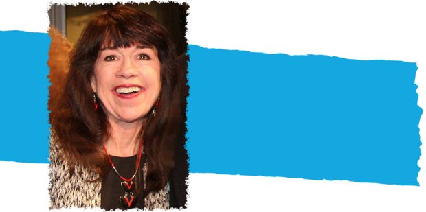 Joanna Sherman smiles directly into the camera, a splash of blue behind her.