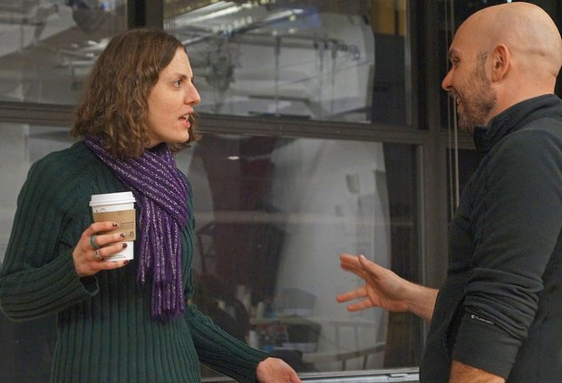 Andrea Hiebler, a cup of coffee in her hand, looks at Rob Askins with an expression of confusion on her face as he explains something to her.