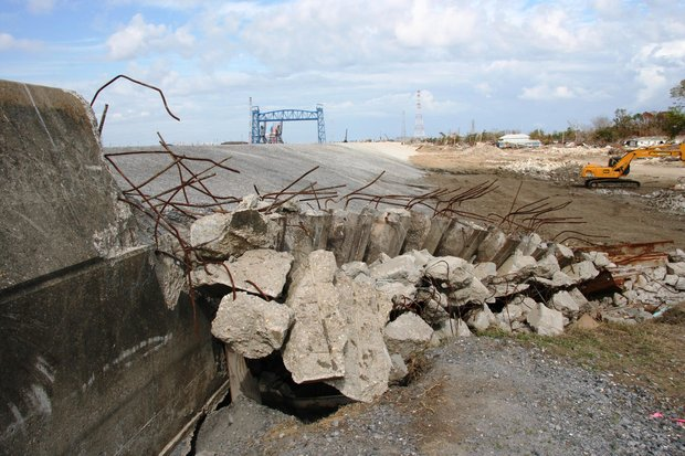 A levee break. Close up, a pile of broken concrete with a pile of dirt sliding down behind it. IN the distance, a bridge and bulldozer.