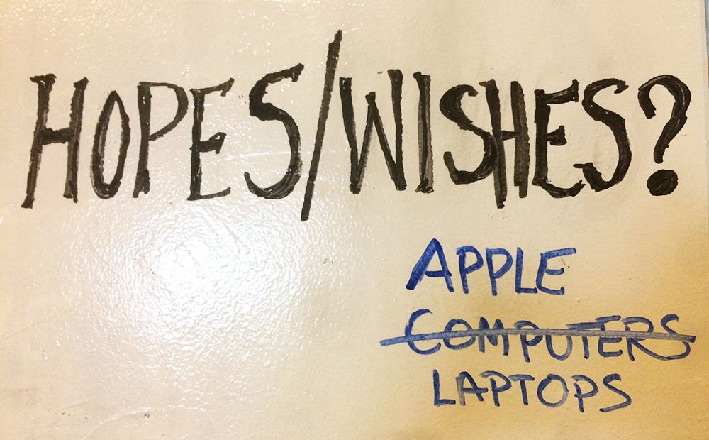 "A section of a dry erase board with the words ""Hopes/Wishes"" written on it in big black block letters. Underneath, ""APPLE LAPTOPS"" is written in blue. The word ""Computers"" is written in blue as well, and has been crossed out."