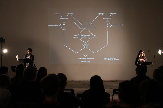 a projection shows a graph of intersecting lines and words. On either side of the screen a man and woman stand at music stands with microphones.