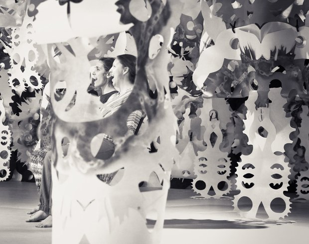 Black and white photo, a stage filled with paper cutouts, resembling paper snowflakes but bigger and in different shapes and structures. Two women are obscured by the structures.