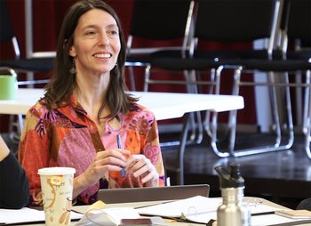 Playwright Andrea Thome sits at a table with a pen in her hand.