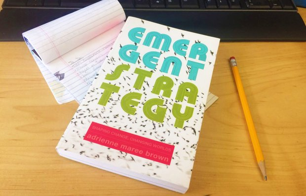 A copy of Emergent Strategy lies on a desk in front of a notepad and keyboard.