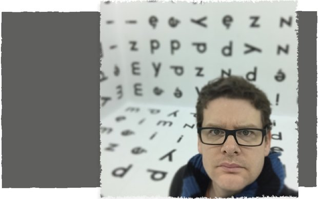 Brian James Polak stares directing into the camera, which shoots him from an angle above him. Behind Brian is a room wallpapered floor to ceiling with letters of the alphabet.