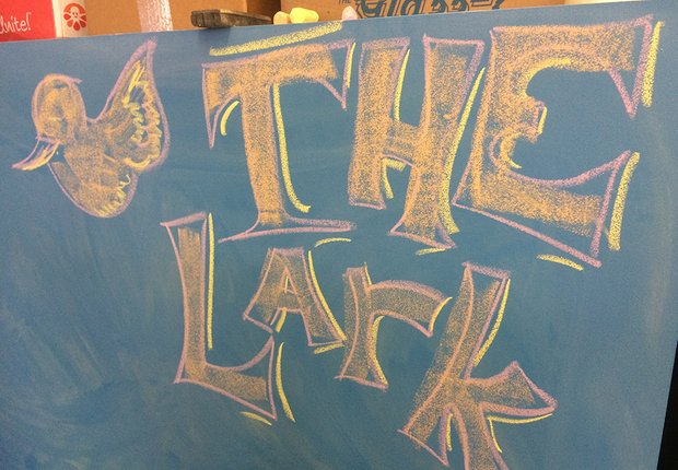"On a blue chalkboard wall, ""The Lark"" is written in large, pink and yellow block letters, in chalk, accompanied by a chalk doodle of a bird."