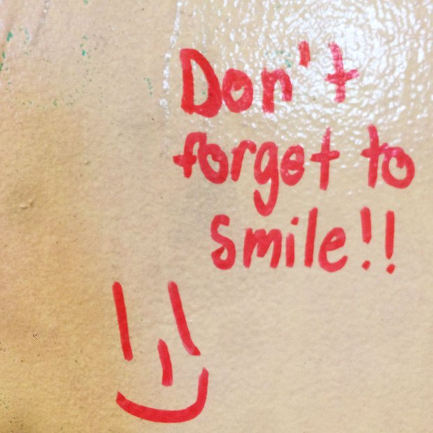 "dry erase board reads ""Don't forget to smile"" with a picture of a smiley face."