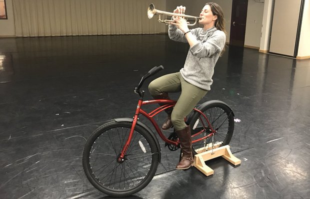 A woman sits on a red bike in an empty studio. The bike is held stationary by a piece of wood on the back wheel, and the woman plays a trumpet.