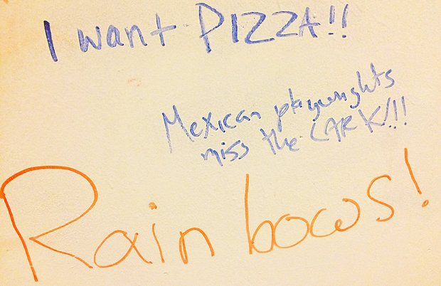 "blue and orange marker on dry erase board reads ""I Want Pizza!!"" ""Mexican playwrights miss the Lark"" and ""Rainbows!"""