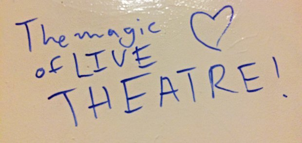 "blue marker on dry erase board reads ""the magic of LIVE THEATER"". a blue heart is drawn next to it."