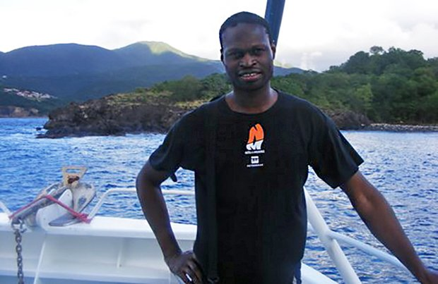 Oladipo Agboluaje stands at the back of a boat. An anchor, hitched up at the stern, is visible, along with water and green hills beyond it.
