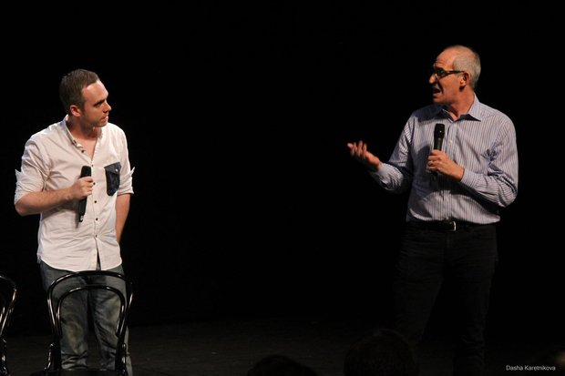 Evgeny Kazachkov and John Eisner on stage against a black background. Each holds a microphone. John talks into his, facing Evgeny.