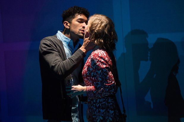 A man and a woman about to kiss on a stage, darkly lit with blue.
